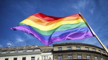 Regenbogenflagge vor blauem Himmel über Gebäude