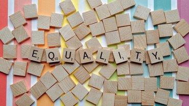 Equality / Gleichheit - beschriftete Holzklötze vor Pride-Flag